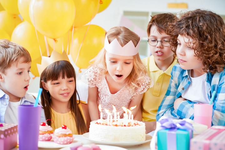 Kinder, Geburtstagskind mit Krone am Kopf bläst die Kerzen aus